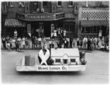 People observe Wilkins Lumber Co. Float during parade